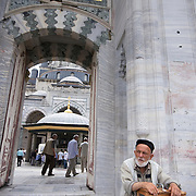 Old man selling small souvenirs at mosque entrance at Istanbul