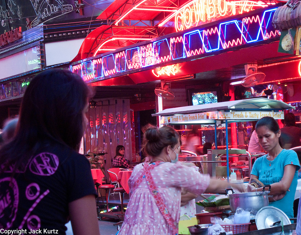 """Mar. 21, 2009 -- BANGKOK, THAILAND: A noodle cart does business with some of the workers on """"Soi Cowboy"""" one of the adult entertainment districts in Bangkok, Thailand.  Photo by Jack Kurtz"""