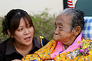 A great granddaughter speaks with her great grandmother Matsu Zakimi, 97, during her birthday celebration at a nursing home near Ogimi Village. Shortly thereafter the young woman applies purple eyeshadow to the woman's eyelids before official birthday photographs. Most of the community has turned out to honor the birthdays of three residents, (These are traditional Japanese birthdays, not the actual birth dates?88, for example is celebrated on the eighth day of the eighth month in the lunar calendar.) Musicians, dancers, and comedians perform as well wishers cheerfully gorge on sushi, fruits, and desserts washed down with beer and saki. (Supporting image from the project Hungry Planet: What the World Eats.)