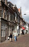 Man and child walking down historic street Nieuwstraat, Dordrecht, Netherlands