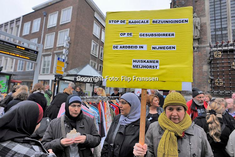 Nederland, Nijmegen, 27-10-2010  Protestaktie bij het gemeentehuis van mensen die protesteren tegen de bezuinigingen en hervormingen op gesubsidieerde arbeid, het werkvoorzieningsschap WNO .De gemeentelijke bezuinigingen, zijn een gevolg zijn van kortingen door de regering. Protest van mensen met een afstand tot de arbeidsmarkt. Bij het gemeentehuis van Nijmegen voerden vandaag tientallen mensen aktie tegen het verdwijnen van 800 gesubsidieerde banen. Veelal mensen die op de arbeidsmarkt weinig kansen hebben. Het publiek kon een petitie tekenen om te proberen de maatregel terug te draaien. De stichting Overal, die gebruikte goederen verkoopt ten bate van de derde wereld, gaf gratis spullen weg. Het gemeentebestuur wil die stoppen als voorschot op de te verwachten maatregelen en bezuinigingen van het kabinet RutteFoto: ANP/ Hollandse Hoogte/ Flip Franssen
