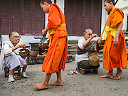 "12 MARCH 2016 - LUANG PRABANG, LAOS: Lao women gives alms to Buddhist monks during the morning tak bat in Luang Prabang. Luang Prabang was named a UNESCO World Heritage Site in 1995. The move saved the city's colonial architecture but the explosion of mass tourism has taken a toll on the city's soul. According to one recent study, a small plot of land that sold for $8,000 three years ago now goes for $120,000. Many longtime residents are selling their homes and moving to small developments around the city. The old homes are then converted to guesthouses, restaurants and spas. The city is famous for the morning ""tak bat,"" or monks' morning alms rounds. Every morning hundreds of Buddhist monks come out before dawn and walk in a silent procession through the city accepting alms from residents. Now, most of the people presenting alms to the monks are tourists, since so many Lao people have moved outside of the city center. About 50,000 people are thought to live in the Luang Prabang area, the city received more than 530,000 tourists in 2014.       PHOTO BY JACK KURTZ"