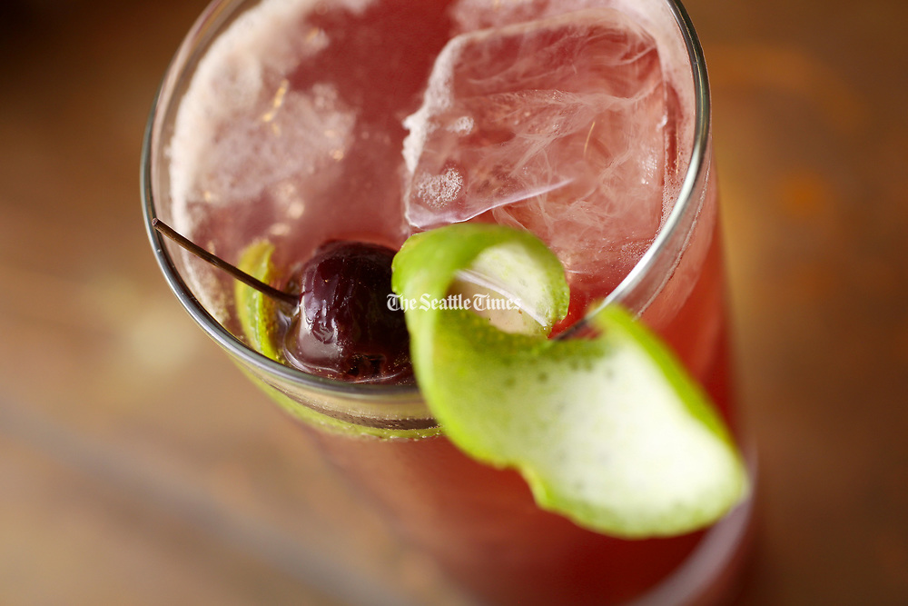 A maraschino is seen in a drink. (Ken Lambert / The Seattle Times)