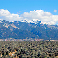USA, New Mexico, Taos County.  Scenic drive north of Taos provides numerous glimpses of Mt. Wheeler and the Taos Mountain Range on a clear winter's day.