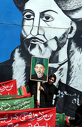KABUL,AFGHANISTAN - SEPT. 9: An Afghan woman holds a photo of Afghan's interim President Hamid Karzai during a ceremony in Kabul Sports Stadium September 9, 2002  to comemerate the anniversary of the death of Ahmad Shah Massoud in Kabul, Afghanistan. (Photo by Ami Vitale/Getty Images)