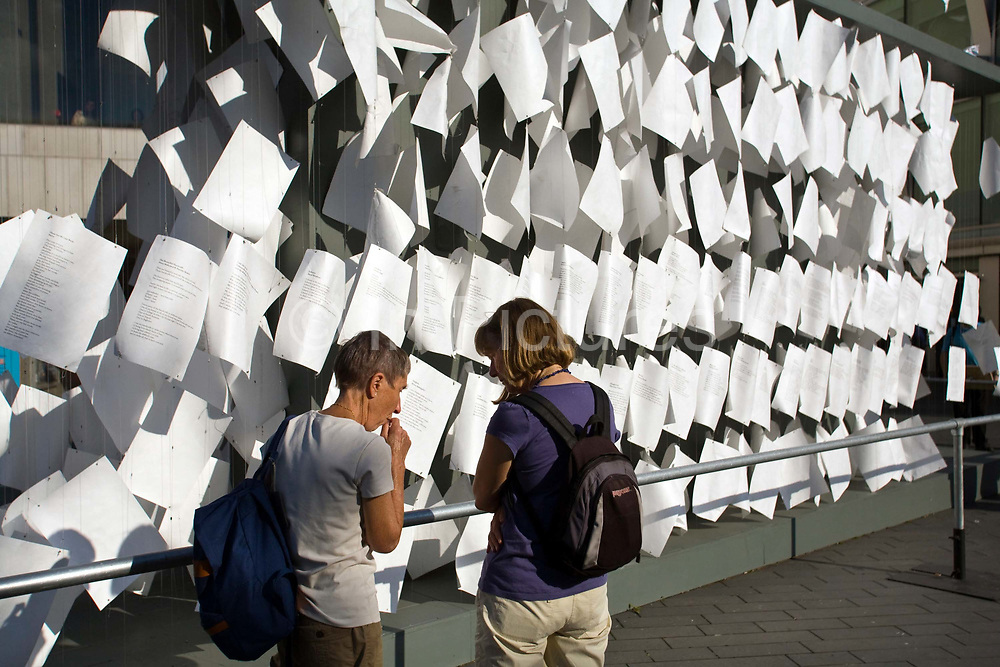 Two women study and stand by an art installation outside the Royal Festival Hall on the South Bank, London, UK