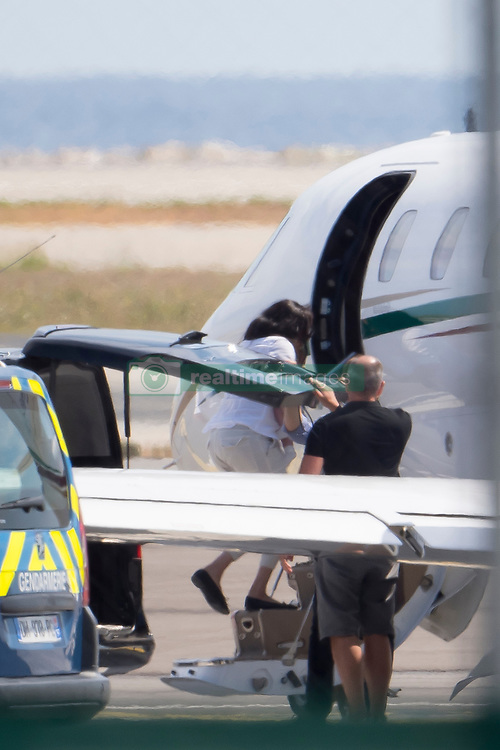 *PREMIUM EXCLUSIVE* Prince Harry, wife Meghan and baby Archie leave the South of France after a three-day family holiday at Sir Elton John's stunning Pounds 15 million summer 'palace.' The Royal couple have come under heavy criticism and been accused of hypocrisy for using private jets three times in the space of eights days for jaunts around Europe while purporting to be 'eco warriors.' The flights are estimated to have emitted at least six times more carbon dioxide per person than a scheduled flight. After jetting into Nice Airport on Wednesday, the Duke and Duchess and baby Archie were whisked off in a Mercedes limousine, with police protection, to Sir Elton's stunning French Riviera villa, Castel Mont-Alban. Considered a summer home by the Rocket Man singer, the sunbeam-yellow hilltop villa boasts commanding views of the Mediterranean from the overlooking tower room. It is high above Nice, with views across the bay and to the Alps and has been used by celebrity pals of Sir Elton, including David and Victoria Beckham. It was originally built in the 1920s as an artists colony. With the help of a team of designers, Elton redesigned the interior to be beautifully and extravagantly decorated in his own flamboyant style, complete with Andy Warhol originals adoring the walls. The villa is so huge it can be seen from across the entire bay. Just three days later, early on Saturday (Aug 17) afternoon, the Royal couple again left Nice Airport on the same private plane, and are believed to have flown back to the UK. Meghan wore a crisp white shirt and matching white trousers as she boarded the 12-seater Cessna aircraft carefully clutching three-month-old Archie Mountbatten-Windsor closely to her chest. Harry, wearing a white polo, jeans, and brown chukka boots, climbed the steps a few moments later, before the plane left for its likely return journey to Farnborough airfield in Hampshire. It was the third time in just over a week that Harry has used a private jet