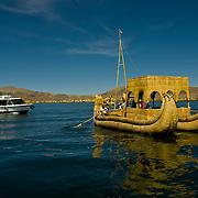 South America, Peru, Andes, Lake Titicaca, Uros, Uros Islands. Reed boats of the Uros Islands (Islas Uros) ply the calm waters of lake Titicaca, Peru.