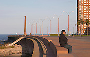 Coast line walk with a single lone man sitting in the dawn sunshine in profile wearing sun glasses. Several lamp post forming a pattern and a chimney in the background. A man walking. Montevideo, Uruguay, South America