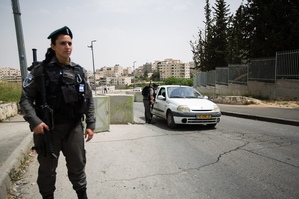 Israeli Border Police Woman Staff Sergeant Chen Cohen (R) inspects vehicles at the exit of the East Jerusalem neighborhood of Issawiya as Corporal Mor Hadad (L) stands guard, in Jerusalem, Israel, on April 10, 2016.