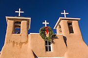 Historic San Francisco de Asis Mission Church decorated with a Christmas wreath in Ranchos de Taos Plaza, Taos, New Mexico. The adobe church built in 1772 and made famous in paintings by artist Georgia O'Keeffe.