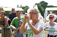 """Photo by Andrew Tobin/Tobinators Ltd - 07710 761829 - Aimi Bresler of the """"Brides to P"""" team takes aim during the World Peashooting Championships held at Witcham, Cambridgeshire, UK on 13th July 2013. Run in conjunction with the village fair, the Championships have been held in Witcham since 1971 when they were started by a Mr Tyson, the village schoolmaster, in order to raise funds for the village hall.Competitors come from as far afield as the USA and New Zealand to attempt to win the event. The latest technology is often used, including laser sights and titanium and carbon fibre peashooters. All peashooters must conform to strict length rules, not exceeding 12 inches, and have to hit a target 12 feet away. Shooting 5 peas at a plasticine target attached to a hay bale, the highest scorers move through the initial rounds to a knockout competition, followed by a sudden death 10-pea shootout."""