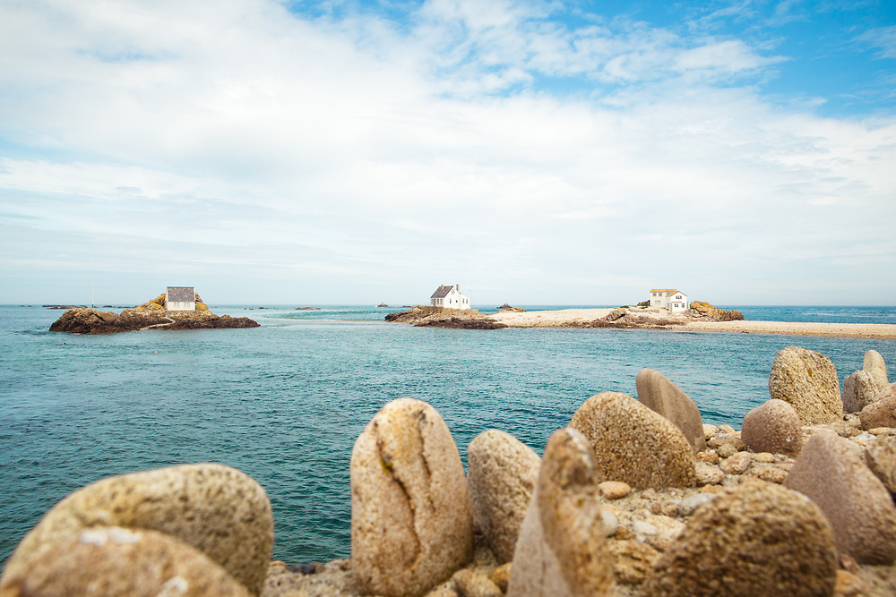 Calm water surrounding the pebbly beach and rocks at the Ecrehous off the coast of Jersey, CI