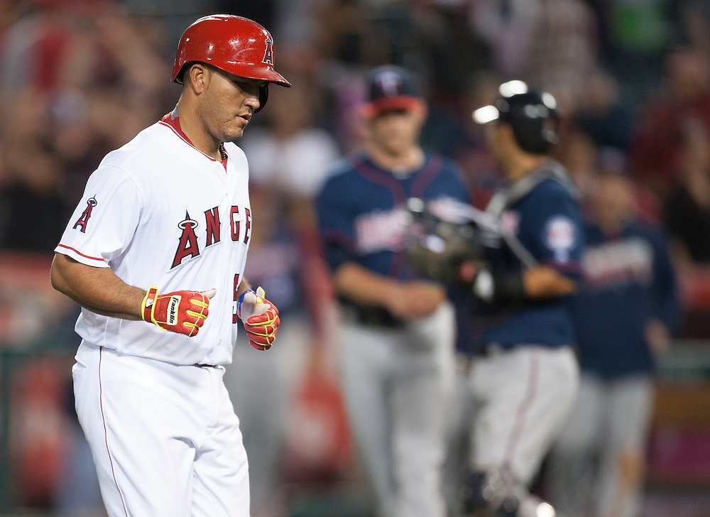 The Angels' Carlos Perez heads to the dugout as the Twins celebrate after making the final out of the Angels 9-4 loss to the Minnesota Twins Monday at Angel Stadium.<br /> <br /> ///ADDITIONAL INFO:   <br /> <br /> angels.0614.kjs  ---  Photo by KEVIN SULLIVAN / Orange County Register  -- 6/13/16<br /> <br /> The Los Angeles Angels take on the Minnesota Twins Monday at Angel Stadium.
