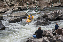 Unidentified spectators watch B. J. Browning of St. Charles, Missouri as Browning races in the K1 men's senior plastic class during the slalom course of the 42nd Annual Missouri Whitewater Championships. Browning placed third place in the class. The Missouri Whitewater Championships, held on the St. Francis River at the Millstream Gardens Conservation Area, is the oldest regional slalom race in the United States.
