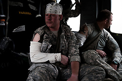 """Two American soldiers with minor wounds from an IED that damaged their armored vehicle are taken to the military hospital at Kandahar Airfield. Scenes from the medical evacuations of wounded Americans, Canadians, and Afghan civilians and soldiers being flown by Charlie Co. 6th Battalion 101st Aviation Regiment of the 101st Airborne Division. Charlie Co. - which flies under the call-sign """"Shadow Dustoff"""" - flies into rush the wounded to medical care out of bases scattered across Oruzgan, Kandahar, and Helmand Provinces in the Afghan south. These images were taken of missions flown out of Kandahar Airfield in Kandahar Province and Camp Dwyer in Helmand Province."""