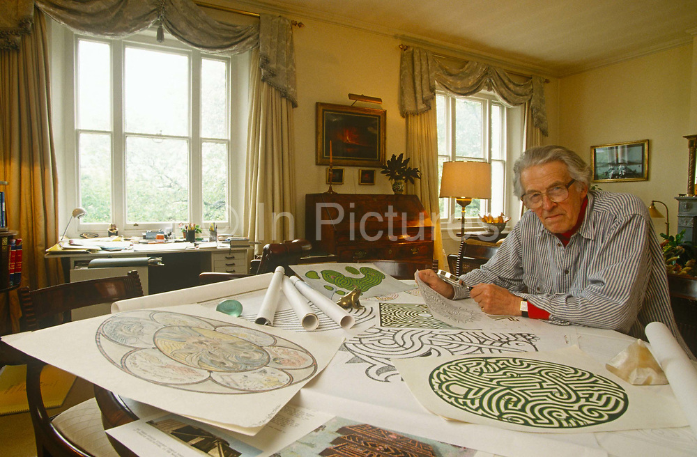 """The renowned maze designer Randoll Coate works in his studio on more labyrinth plans. Gilbert Randoll Coate (8 October 1909 – 2 December 2005) was a British diplomat, maze designer and """"labyrinthologist"""". With interests in art and history, Coate completed over 50 new mazes in Britain and around the world. His designs are particularly noted for their symbolism. Although it is rarely possible to see a large maze in plan view, they would often incorporate hidden shapes and references of significance to the clients who had commissioned the maze. Notable work includes: Bath Festival Maze (1984) — a stone path in Beazer Gardens, Bath; a yew hedge maze at Blenheim Palace for the Duke of Marlborough; El laberinto de Borges (Borges Memorial Maze) — San Rafael, Mendoza, Argentina. He died in Le Rouret, near Grasse, France on the 2 December 2005, aged 96."""