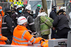 © Licensed to London News Pictures.28/01/2021, London,UK. An activist is being detained by the police while the eviction of HS2 Rebellion group from Euston Square Gardens in central London began yesterday and continues today. It is reported the protesters have built a 100ft tunnel under the gardens and are protesting against the HS2 train line development Photo credit: Marcin Nowak/LNP