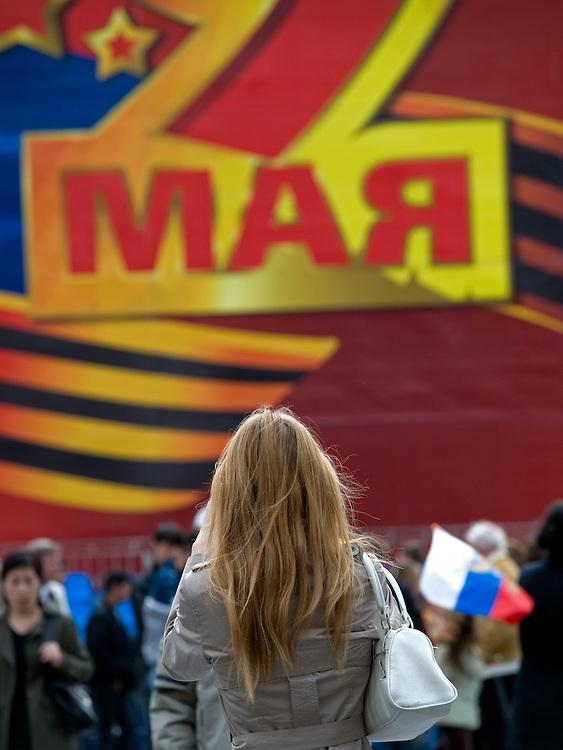 Junge Frau vor der für die Militärparade aufgebauten Tribüne und monumentalen Dekoration auf dem Roten Platz am Tag der großen Siegerparade. <br /> <br /> Young woman infront of the big tribune and monumental decoration prepared for the Military Parade at Red Square during the day of the Victory Parade in Moscow.
