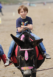 © Licensed to London News Pictures. 27/05/2013..Saltburn, England..A youngster enjoys a donkey ride on the beach at Saltburn by the Sea in Cleveland during the warm bank holiday....Photo credit : Ian Forsyth/LNP