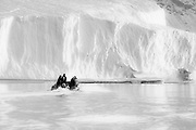 Tourists in a zodiac approaching an iceberg in arctic landscape along the east coast of Greenland, black and white,Scoresby Sound, East Greenland