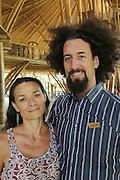 """Zach, is a teacher at Green School, he is pictured with his wife Sophie Daubisse. Their two sons Milan is 12 years old, Sevan-Fidel is 9 years old, who are students at Green School. They are french residents<br /><br />The Green School (Bali) is one of a kind in Indonesia. It is a private, kindergarten to secondary International school located along the Ayung River near Ubud, Bali, Indonesia. The school buildings are of ecologically-sustainable design made primarily of bamboo, also using local grass and mud walls. There are over 600 students coming from over 40 countries with a percentage of scholarships for local Indonesian students.<br /><br />The impressive three-domed """"Heart of School Building"""" is 60 metres long and uses 2500 bamboo poles. The school also utilizes renewable building materials for some of its other needs, and almost everything, even the desks, chairs, some of the clothes and football goal posts are made of bamboo.<br /><br />The educational focus is on ecological sustainability. Subjects taught include English, mathematics and science, including ecology, the environment and sustainability, as well as the creative arts, global perspectives and environmental management. This educational establishment is unlike other international schools in Indonesia. <br /><br />Renewable energy sources, including solar power and hydroelectric vortex, provide over 50% of the energy needs of the school. The school has an organic permaculture system and prepares students to become stewards of the environment. <br /><br />The school was founded by John and Cynthia Hardy in 2008."""