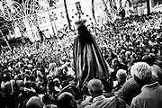 """The Virgin Mary outside of the church.In Ponticelli, the eastern outskirts of Naples, for 250 years, the 5th of August is celebrated the Mother of God with the title of """"Our Lady of the Snows.""""<br /> The statue of the patron is hoisted on top of the """"Wagon"""", the heavy machinery of the party of about 17 meters, carried by hand from less than a hundred men, along the streets of the neighborhood.<br /> The Virgin is enthroned above.<br /> In Via San Rocco the people, without effort, tap the wagon from the balconies, covering it sometimes with confetti.<br /> In Naples, in the places where degradation of culture and traditions are still popular, people condense in the briefest of moments, cyclical, of the party, its history daily, made of sweat, hopes, disappointments, fatigue, illness. The party therefore assumes a character of inevitability for its ability to signify all the painful complexity of life."""