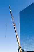 USA, Alaska, Anchorage, A construction crane looms near an office building in downtown Anchorage.