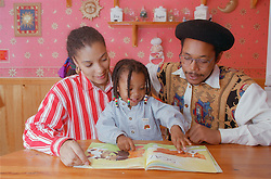 Father and mother sitting at table with young son reading story book,