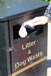 Putting dog dirt into a bin.