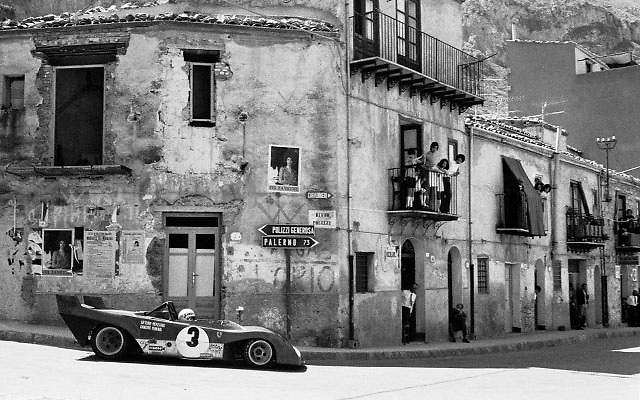 """""""COLLESANO"""" <br /> aka TARGA FLORIO FERRARI<br /> <br /> SICILY, MAY 21, 1972 ... There we were, idling away a warm springtime day in the ancient Mediterranean town of Collesano, when we heard the 20th Century coming down on us. Something was plunging from the craggy mountains above, something wild, its untamed cry reverberating between the timeworn buildings. The wise among us took cover in doorways. I raised my Nikon. Around the corner, a flash of scarlet. The Ferrari. I framed and fired. And the moment was gone.<br /> <br /> For me this picture brings it all back, and it also seems to speak to many who were never there but wish they had been. Visitors in our vendor booth at Monterey often pick it up to show their friends, and they talk about it with animation and shining faces.<br /> <br /> A blood-red racing car screaming across the open landscapes of Olde Europe. The mad delirium that sparked our passion.<br /> <br /> This was the crazy-wonderful old Targa Florio, one of the world's most venerable road races, and among the most endangered. It had been going for 66 years when I was there in 1972, but that was its next to last year as an important International event.  Too dangerous, was the bleat coming from all sides. Sure, it was, but so what? I went there to stand up for it.<br /> <br /> For me, that day remains one of the most magical  I ever spent at motor racing. <br /> <br /> Though we colloquially call this picture just """"Collesano,"""" its proper file ID is SC72Targa_Ferrari3CollesanoB"""