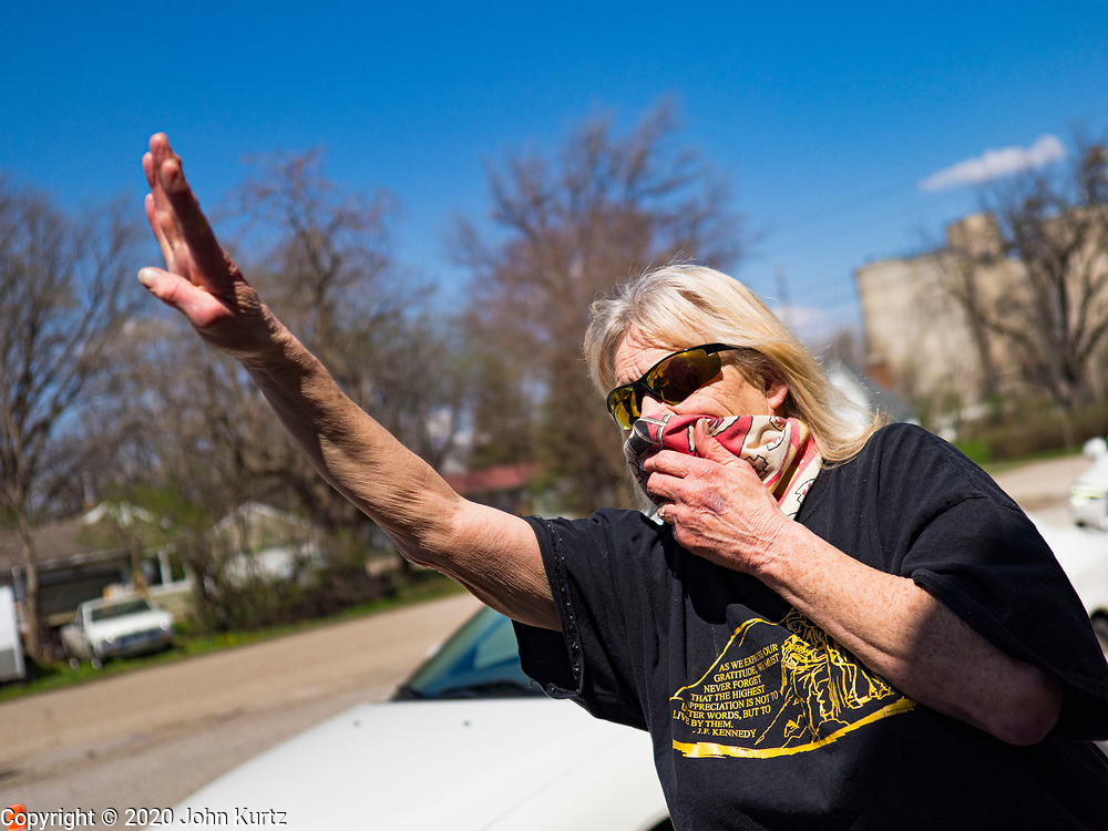 """26 APRIL 2020 - JEWELL, IOWA: PEG THOMPSON, wearing a mask because of the COVID-19 pandemic, signals that people in a car want four """"grab and go"""" roast pork dinners in Jewell during a fund raiser Sunday. Jewell, a small community in central Iowa, became a food desert when the only grocery store in town closed in 2019. It served four communities within a 20 mile radius of Jewell. Some of the town's residents are trying to reopen the store, they are selling shares to form a co-op, and they hold regular fund raisers. Sunday, they served 550 """"grab and go"""" pork roast dinners. They charged a free will donation for the dinners. Despite the state wide restriction on large gatherings because of the COVID-19 pandemic, the event drew hundreds of people, who stayed in their cars while volunteers wearing masks collected money and brought food out to them. Organizers say they've raised about $180,000 of their $225,000 goal and they hope to open the new grocery store before summer.           PHOTO BY JACK KURTZ"""