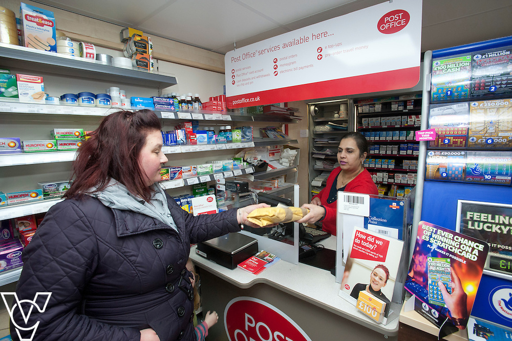Pictured postmaster Kanchan Lakhman serving customer Marie Weston<br /> <br /> Thringstone Post Office, 19-23 Loughborough Road, Thringstone, Leicestershire.<br /> Date: January 23, 2015