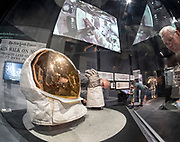 """Dad's charts, maps and photos on display, center, with """"Destination Moon"""" at Seattle's Museum of Flight.  """"Buzz"""" Aldrin's helmet and gloves, left. Above, film showing Apollo 11 astronauts referring to navigation charts."""