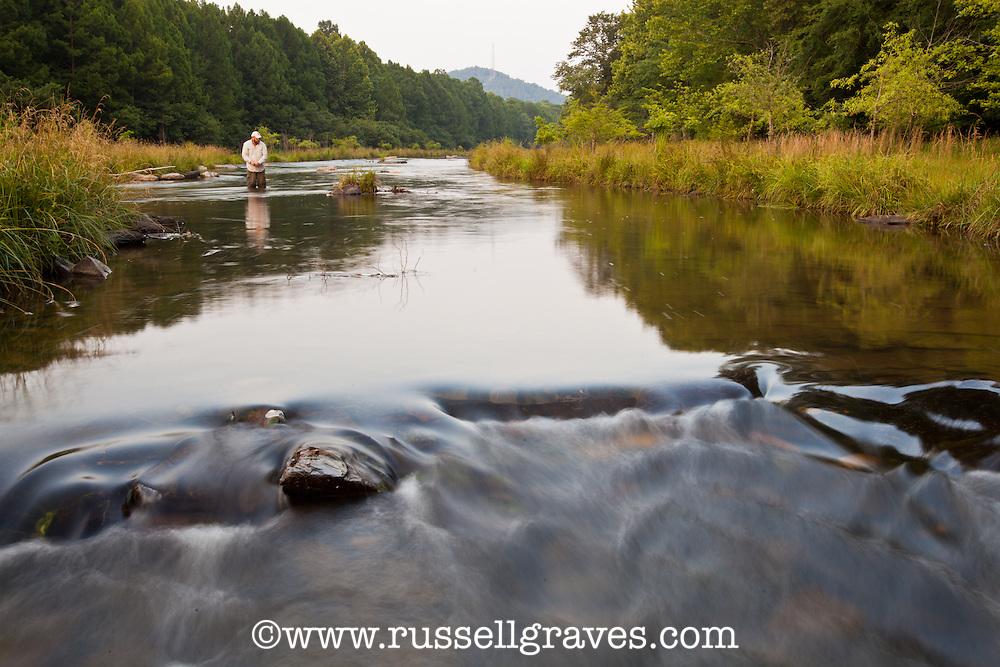 FLY ANGLER WADE FISHING IN THE MOUNTAIN FORK RIVER NEAR BROKEN BOW, OKLAHOMA
