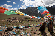 In a brisk morning breeze, two women from a nearby village tie prayer flags along a pilgrim path overlooking a reconstructed Buddist monastery in the Tibetan Plateau. (From the book What I Eat: Around the World in 80 Diets.)  Most of the buildings remain in ruins after being destroyed in the 1960s.