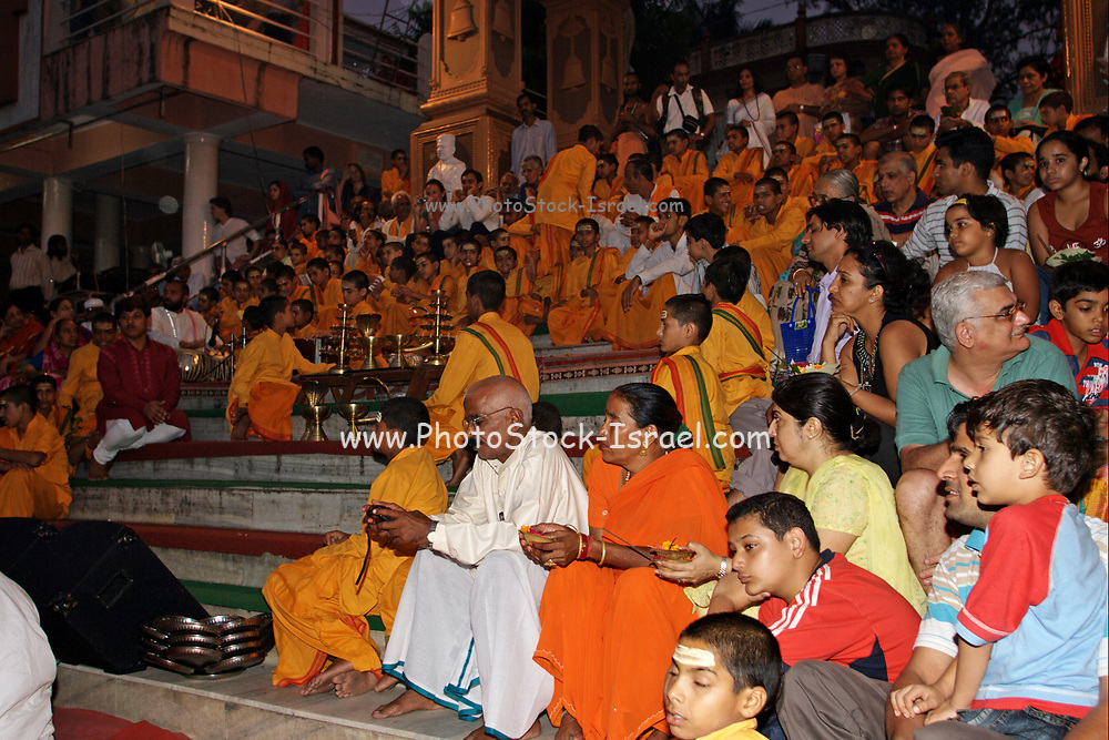 Spectators, Believers, Followers and Priests in orange robes in the holy city of Rishikesh in Uttarakhand, India during the evening light ceremony called Ganga Aarti (or aarthi) to worship river Ganga / Ganges.