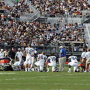Players take a knee for injured Memphis wide receiver Tannar Rehrer (85) during an NCAA football game between the Memphis Tigers and the Central Florida Knights at Bright House Networks Stadium on Saturday, October 29, 2011 in Orlando, Florida. (AP Photo/Alex Menendez)
