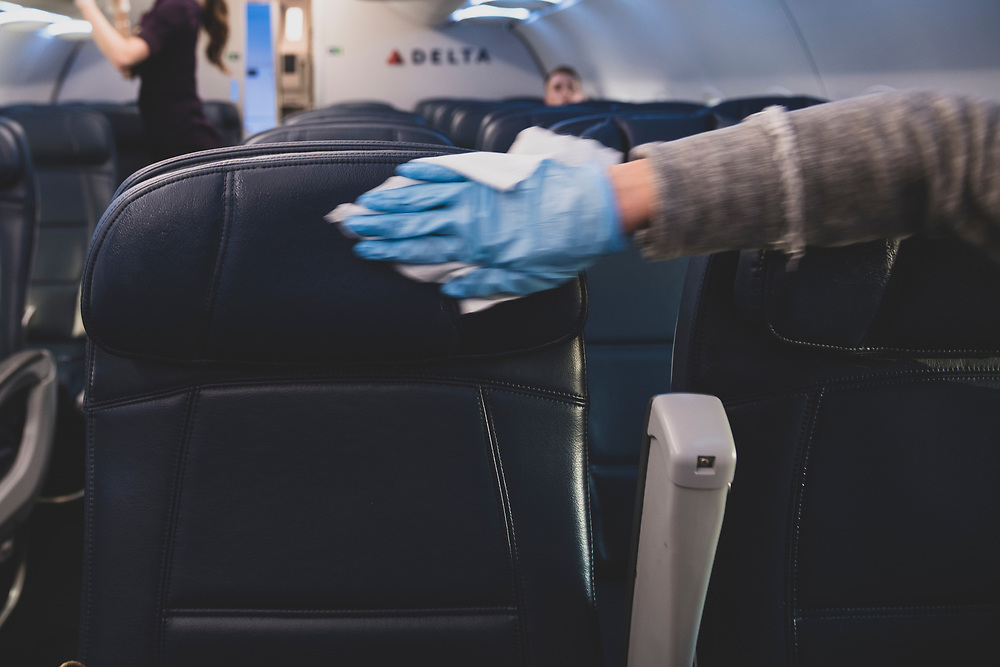 New York City, USA - March 21, 2020: At Laguardia Airport, a passenger who has just boarded the plane wears a plastic glove while using a wipe to disinfect the airplane seats and armrests on her row.