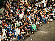 04 NOVEMBER 2016 - BANGKOK, THAILAND: Thais wait to get their clothes dyed black at Krungthai tractor. About 150 volunteers are working at Krungthai Tractor in Bangkok to dye clothes black for people in mourning following the death of Bhumibol Adulyadej, the King of Thailand. The government declared a one year mourning period, during which Thais are encouraged to wear black and a 30 day mourning period during which Thais are very strongly encouraged to wear black. Furthermore, black is mandatory for official mourning functions, including visits to the Grand Palace and Sanam Luang, the public ceremonial ground across the street from the Palace. The expectation to wear black created a shortage of black clothes in many markets and Thailand's poor couldn't afford what black clothes were still available. Community groups have started dyeing clothes for people who either can't find or can't afford black clothes. The clothes dyeing volunteers at Krungthai Tractor were organized by Thai actress Chompoo Araya A. Hargate and Thai fashion blogger Chavaporn Laohapongchana.      PHOTO BY JACK KURTZ