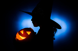 Picture posed by model A young girl in a Halloween costume holds a pumpkin, ahead of Halloween celebrations tomorrow.