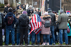 © Licensed to London News Pictures. 12/12/2020. Manchester, UK. A man wears an American flag as a crowd gathers with signs for North Unites protest in Piccadilly Gardens, Manchester. Piers Corbyn is expected to make a speech later. Photo credit: Kerry Elsworth/LNP