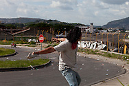 5 July 2009 - Tegucigalpa, Honduras - A supporter of ousted Honduras' President Manuel Zelaya throw rocks at soilders while receiving live fire at the Tegucigalpa airport.  President Zelaya was unable to land today, but pledged to return in the coming days. His supporters have been marching in the capital's streets since he was ousted last Sunday, but the protests have increased dramatically in the last few days.