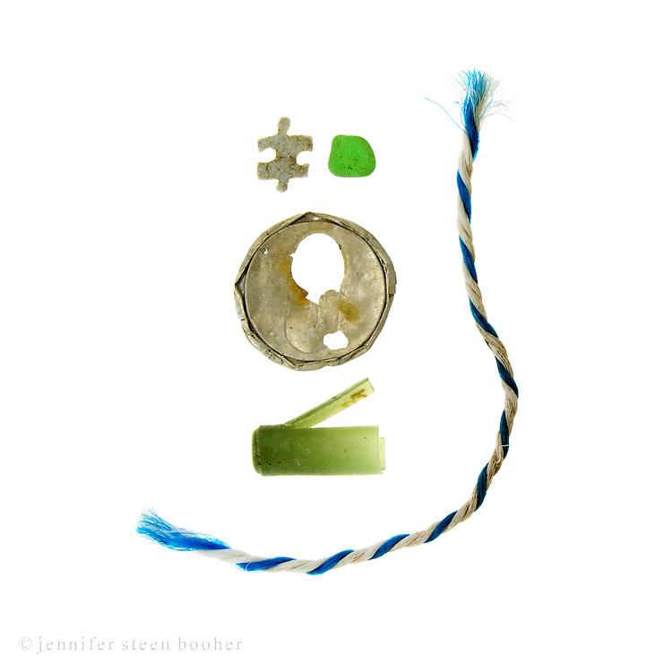 Pulpboard jigsaw puzzle piece, sea glass, aluminum soda can top, shotgun shell, fishing rope.