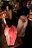 A fishmonger stands next to a piece of tuna in Tsukiji Market, Tokyo, Japan.