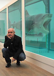 © Licensed to London News Pictures. 02/04/2012. London, UK . Damien Hirst poses in front of 'The Physical Impossibility of Death in the Mind of Someone Living 1991, a 14 ft. shark suspended in formaldehyde. The Tate Modern presents the first substantial retrospective of British artist Damien Hirst. The exhibition tuns 4th April - 9th September at Tate Modern London. Photographers Stephen Simpson/LNP