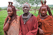 A Himba chief stands with his two wives outside his home in the small village of Okapembambu in northwestern Namibia, during the rainy season in March.  The Himba culture is polygamous. The Himba diet consists of corn meal porridge and sour cow's milk.  Like most traditional Himba women, they covers themselves from head to toe with an ochre powder, cow butter blend.