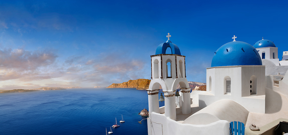 Panoramic  over the traditional Greek Orthodox churches of Oia (ia), Cyclades Island of  Thira, Santorini, Greece.<br /> <br /> The settlement of Oia had been mentioned in various travel reports before the beginning of Venetian rule, when Marco Sanudo founded the Duchy of Naxos in 1207 and feudal rule was instituted on Santorini. n 1537, Hayreddin Barbarossa conquered the Aegean islands and placed them under Sultan Selim II. However, Santorini remained under the Crispo family until 1566, passing then to Joseph Nasi and after his death in 1579 to the Ottoman Empire. .<br /> <br /> If you prefer to buy from our ALAMY PHOTO LIBRARY  Collection visit : https://www.alamy.com/portfolio/paul-williams-funkystock/santorini-greece.html<br /> <br /> Visit our PHOTO COLLECTIONS OF GREECE for more photos to download or buy as wall art prints https://funkystock.photoshelter.com/gallery-collection/Pictures-Images-of-Greece-Photos-of-Greek-Historic-Landmark-Sites/C0000w6e8OkknEb8