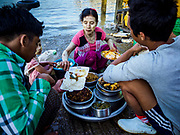 23 NOVEMBER 2017 - YANGON, MYANMAR: A food vender serves customers at the San Pya Fish Market. San Pya Fish Market is one of the largest fish markets in Yangon. It's a 24 hour market, but busiest early in the morning. Most of the fish in the market is wild caught but aquaculture is expanding in Myanmar and more farmed fresh water fish is being sold now than in the past.    PHOTO BY JACK KURTZ