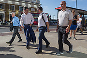 Two men argue as other commuters walk southwards over London Bridge, from the City of London - the capitals financial district - to Southwark on the south bank, on 2nd August 2018, in London, England.
